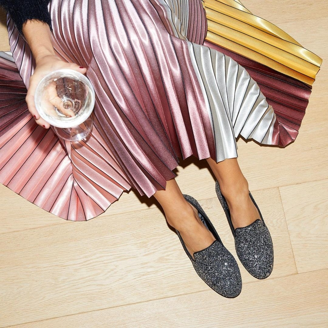 A model wearing the sparkly flats in gunmetal glitter