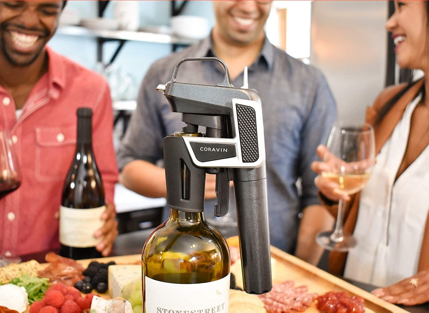 The wine opener on a bottle of wine with people gathered around it drinking glasses of wine