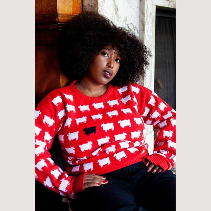 a model wearing the red sweater with sheep on it and one black one