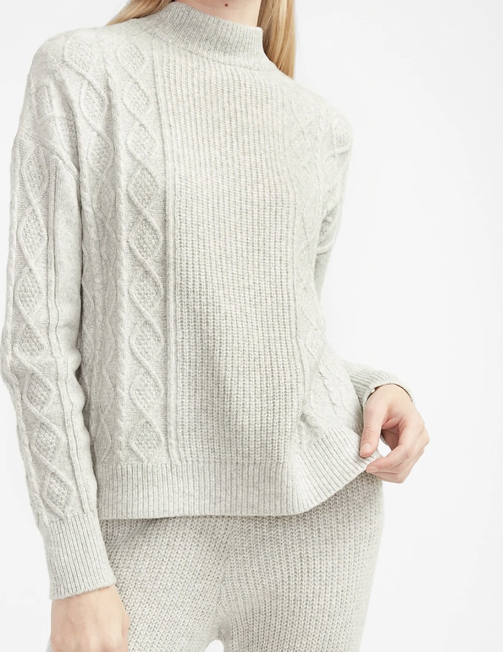 a cable-knit mock-neck sweater in heather gray