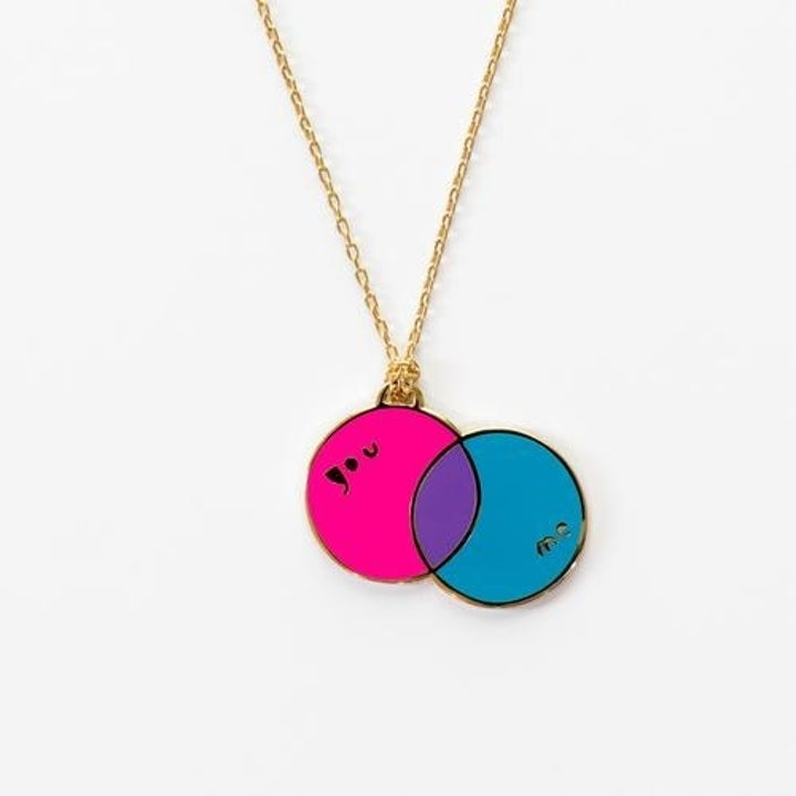 A gold pendant necklace with a pink and blue circle venn diagram