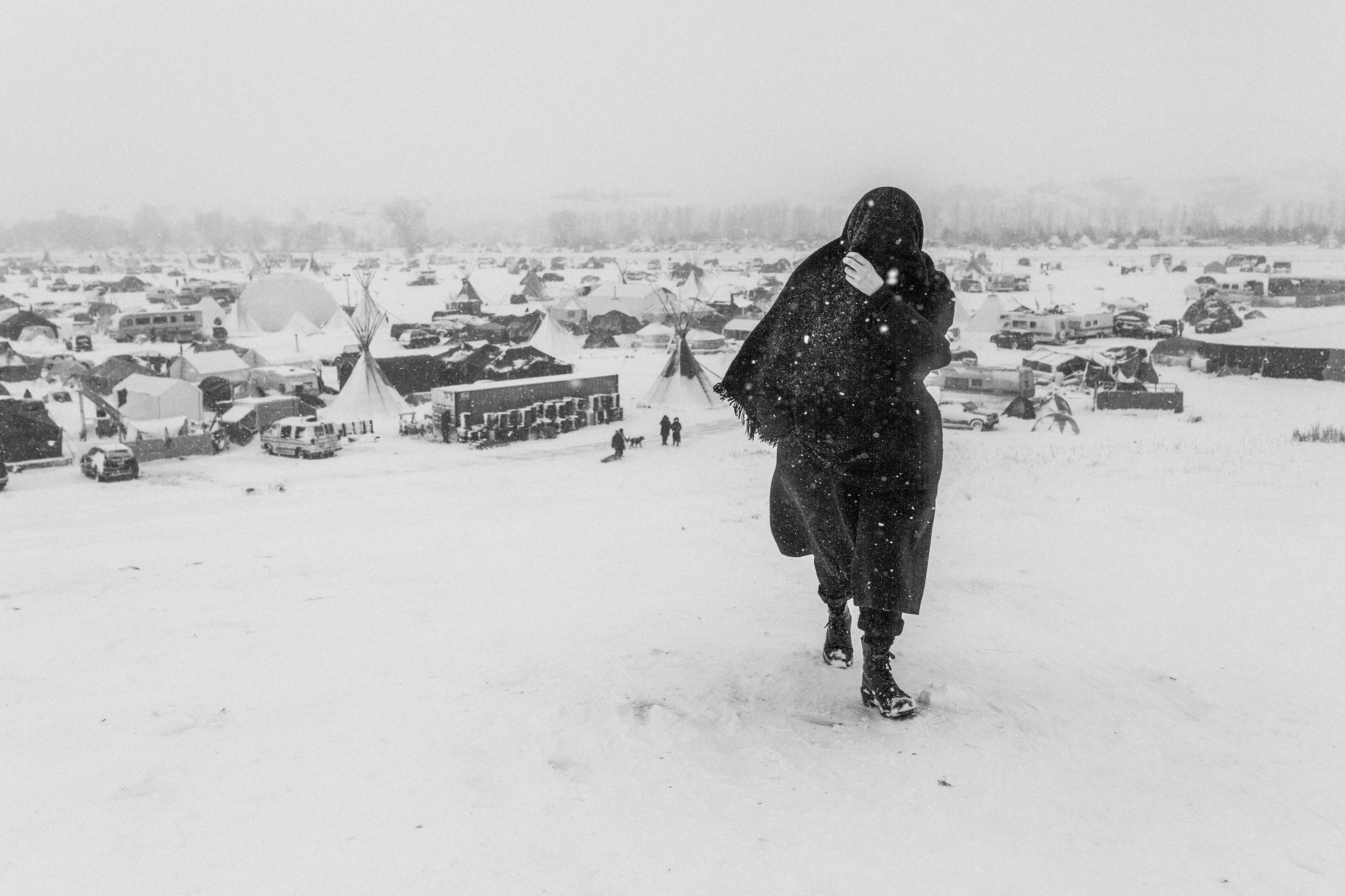 A woman wrapped in black walking away from a snowy landscape with cars, vans, buses, and temporary shelters.