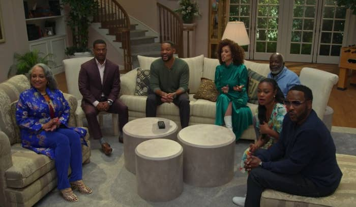"""Daphne Maxwell Reid, Alfonso Ribeiro, Will Smith, Karyn Parsons, Joseph Marcell, Tatyana Ali, and DJ Jazzy Jeff sitting in a replicated living room from """"The Fresh Prince"""""""