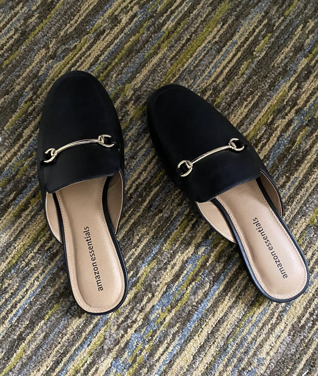 Reviewer image of black mule shoes with a decorative metal buckle on the top of the foot