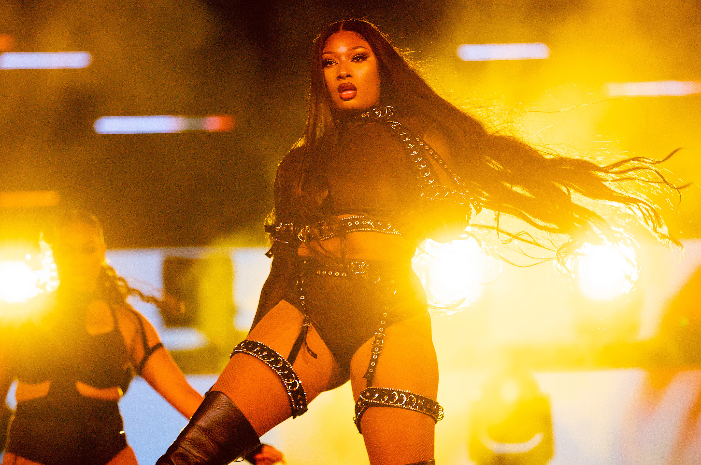 Megan Thee Stallion performing on stage in a black harness outfit and with lights behind her