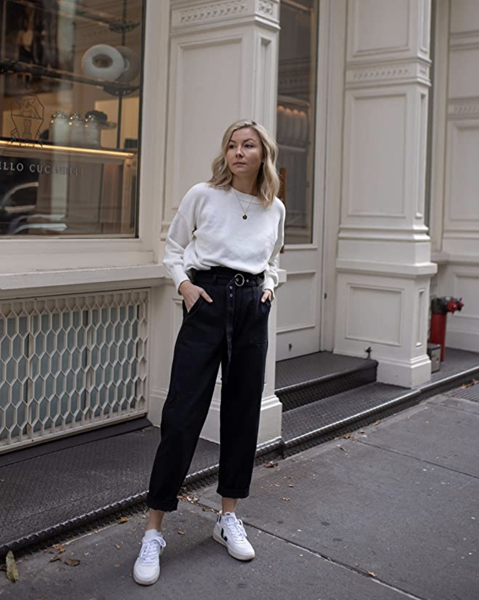 A model in a white sweater with slight balloon sleeves and a crewneck tucked into pants