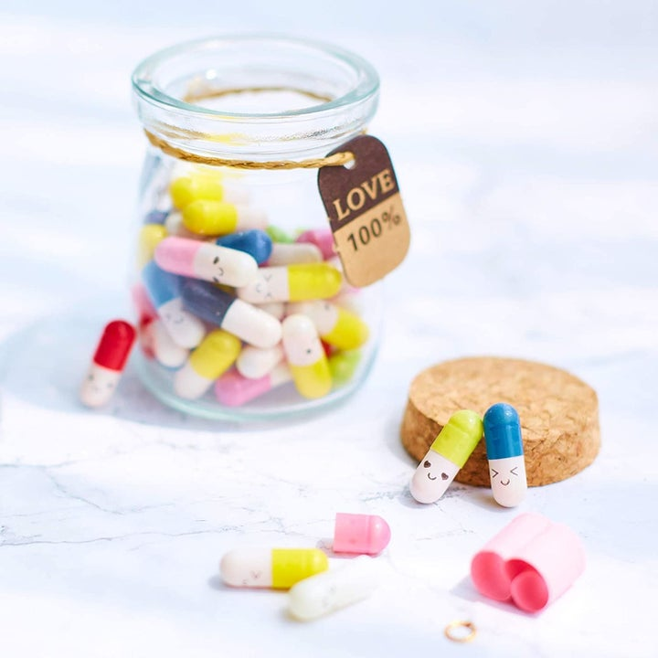 A jar of the capsules with little smiley faces on them
