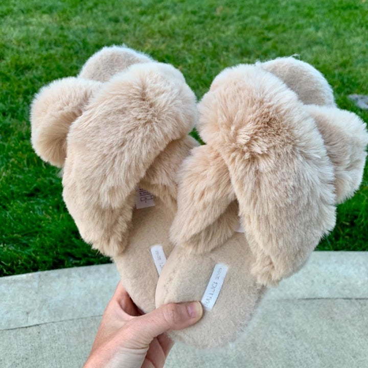 reviewer holding the slippers in beige