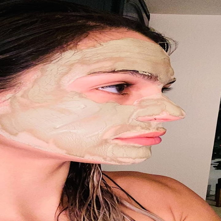 A reviewer wearing the mask which is slightly green