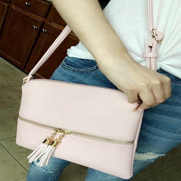 reviewer wearing the bag in pink on their shoulder