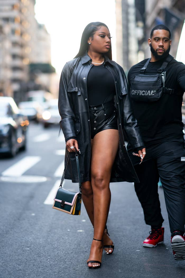 Megan Thee Stallion in shorts and a black trench coat, with a man on her right also in black, in New York