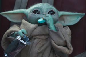 baby yoda eating a blue cookie