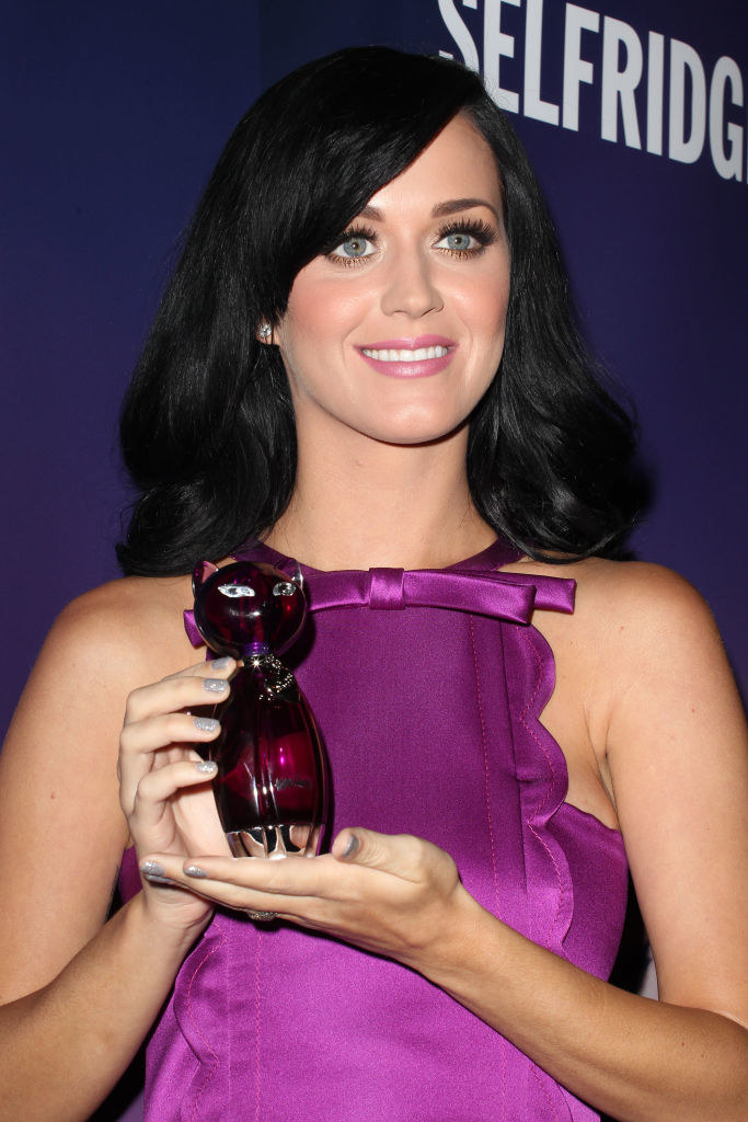 Katy Perry holding up a purple bottle of her perfume which is in the shape of a cat