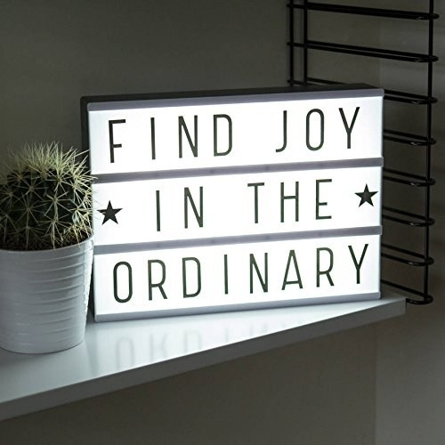 "The lightbox is emitting a white light. The message on it reads, ""Find joy in the ordinary""."