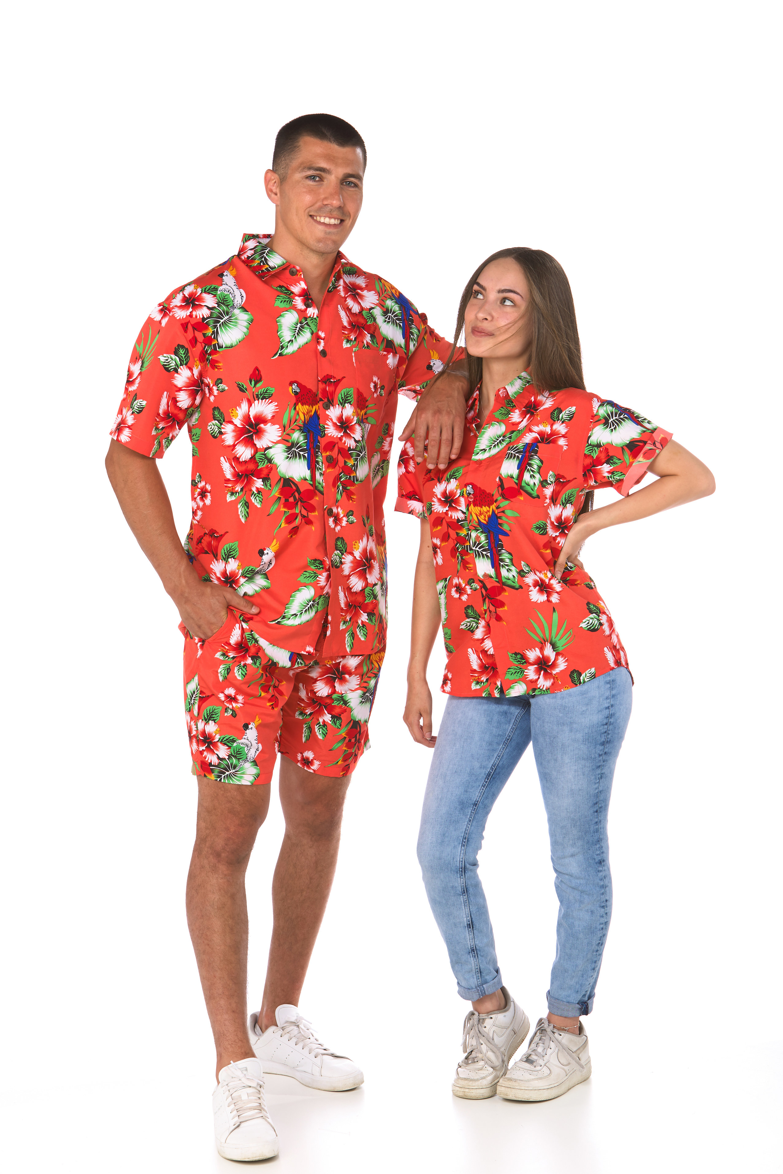 Man and woman pose in matching red Lowes' shirts with hibiscus flowers and parrots