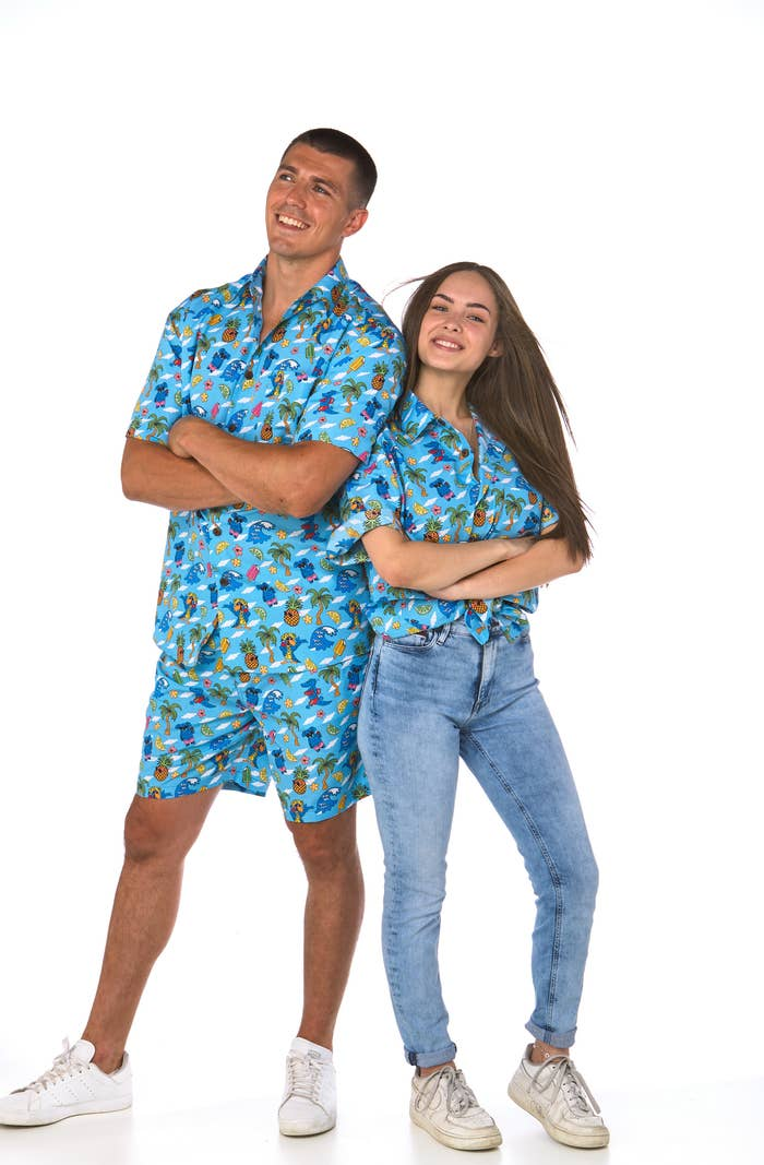 Two people both wearing the same Lowes' shirt decorated with blue koalas, pineapples with sunglasses, waves and palm trees