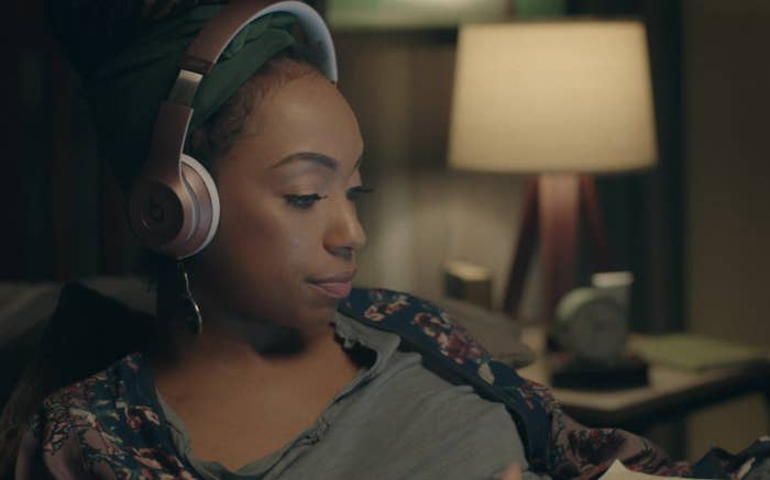 A girl sits on her bed wearing headphones, looking at a laptop.