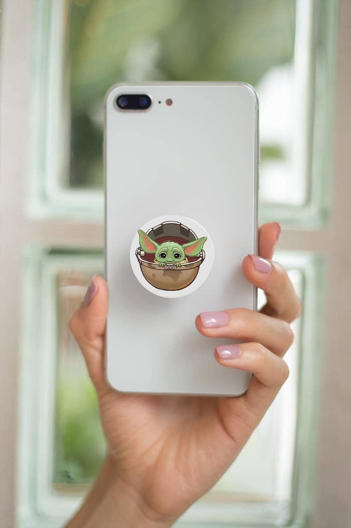 a pop socket with baby Yoda's face on a phone