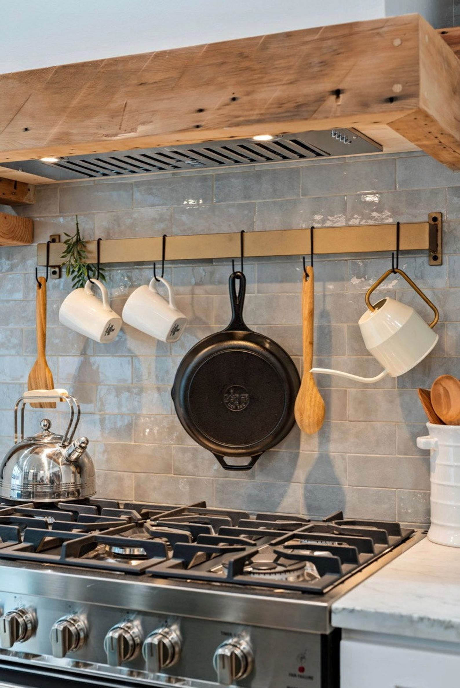 brass rack hung above stone holding utensils, tea kettle, and pans