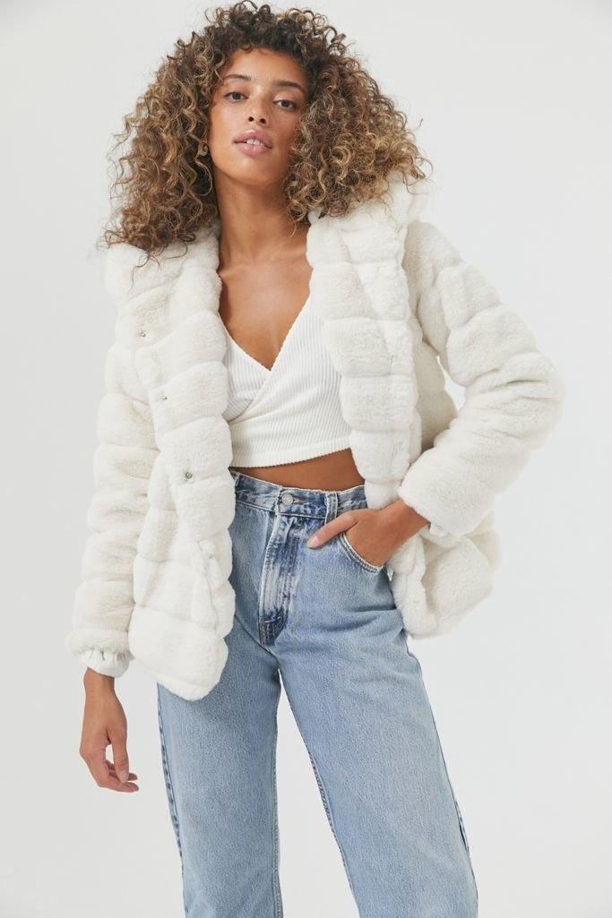 a model wears the apparis goldie vegan faux fur coat in ivory