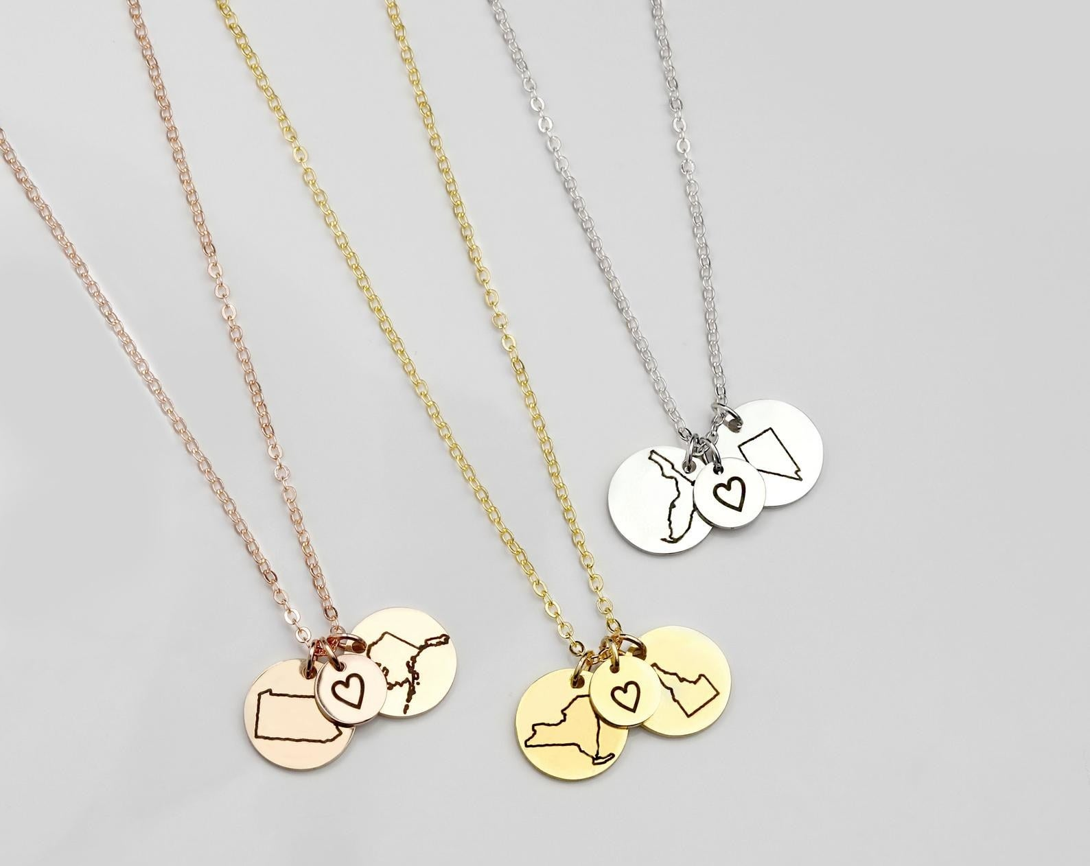 Three bronze, silver, and gold necklaces with pendants of outlines of different U.S. states with a heart pendant in the middle