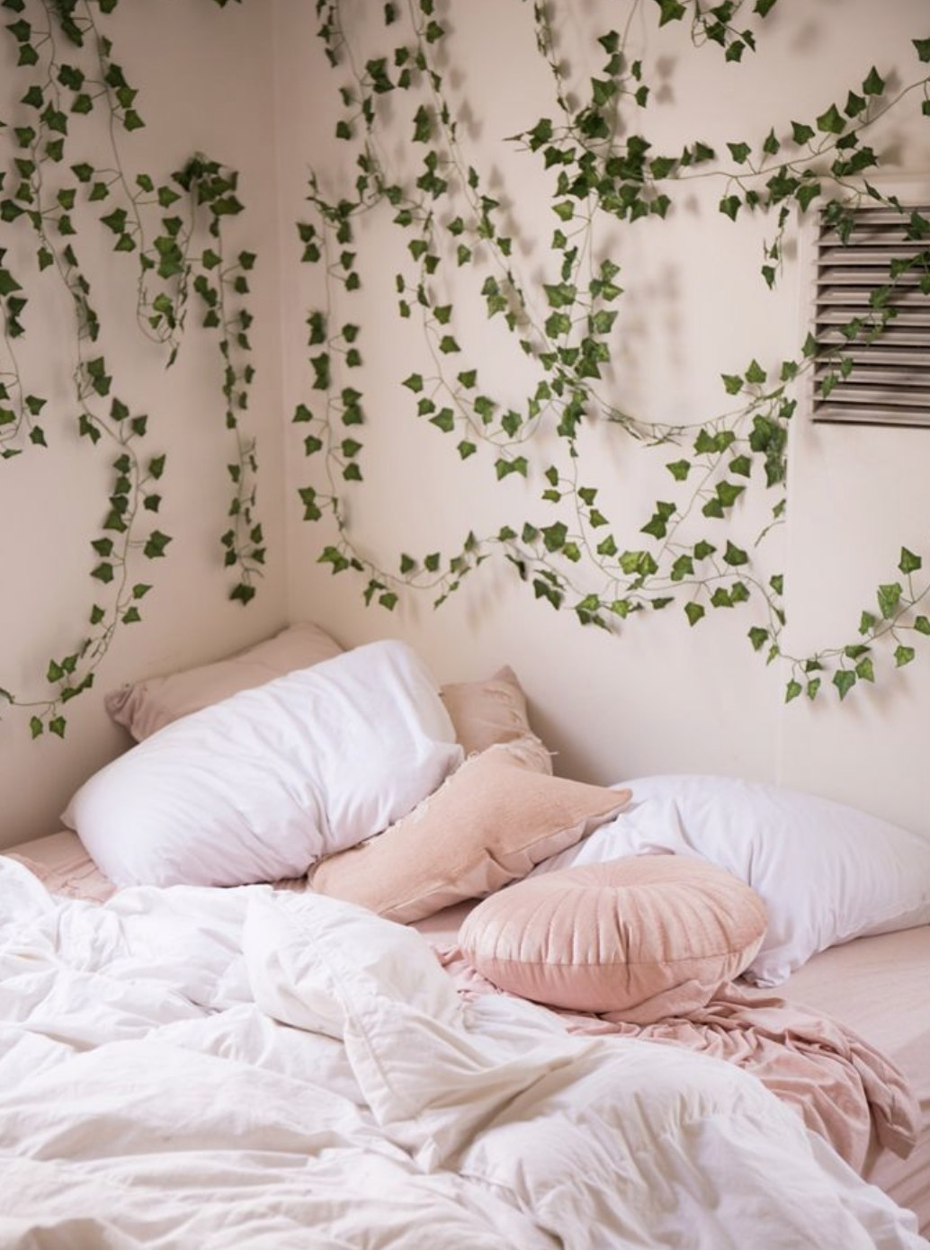 A bedroom with green decorative vines on the wall