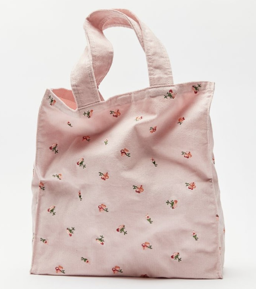 A pink tote bag with embroidered flowers