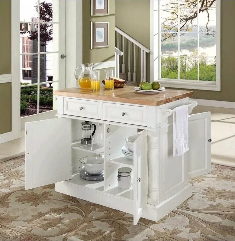 The white kitchen island with a butchers block countertop, drawers, a towel rod, and double-sided cabinets
