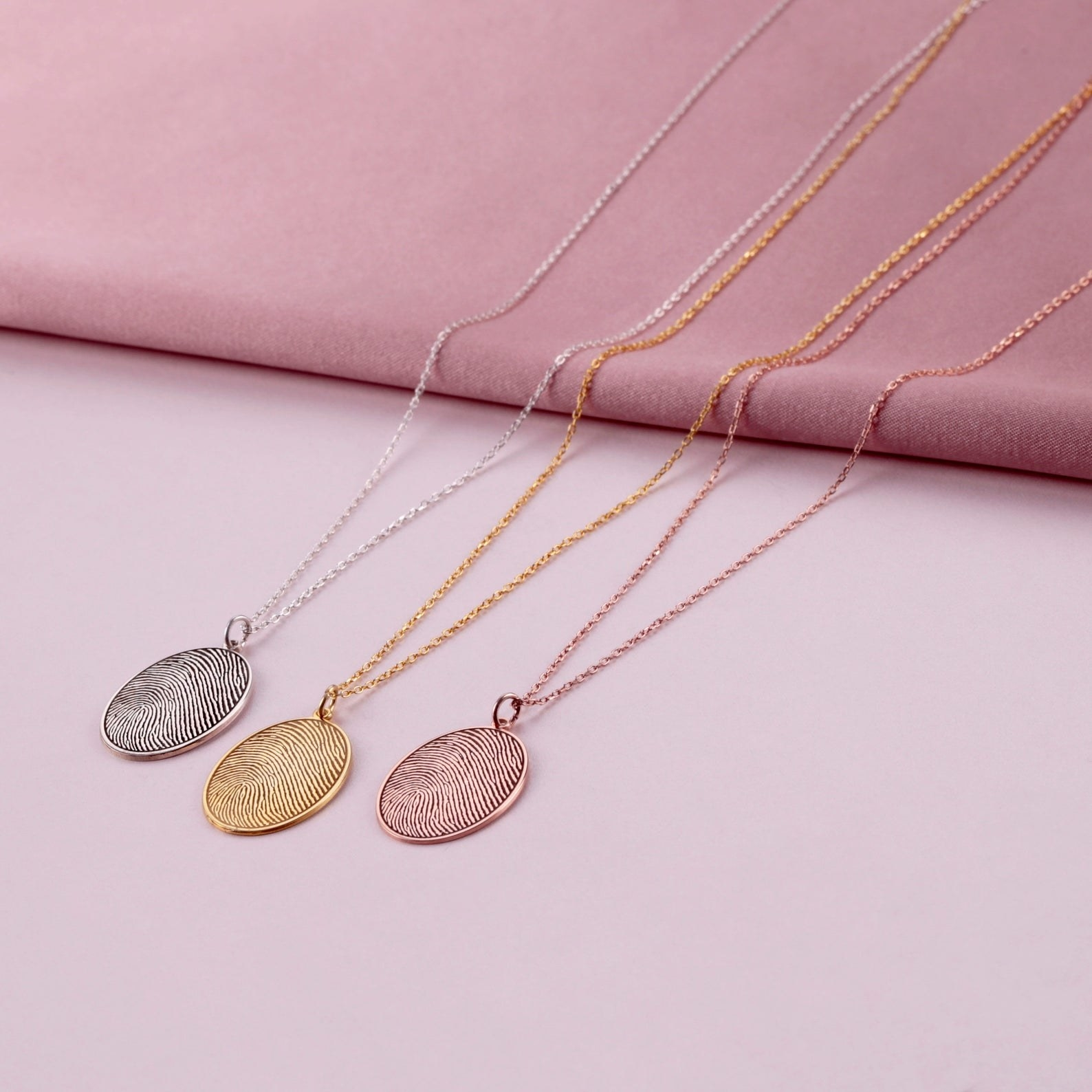 The necklaces in silver, gold, and rose gold each with a fingerprint charm on an oval disc