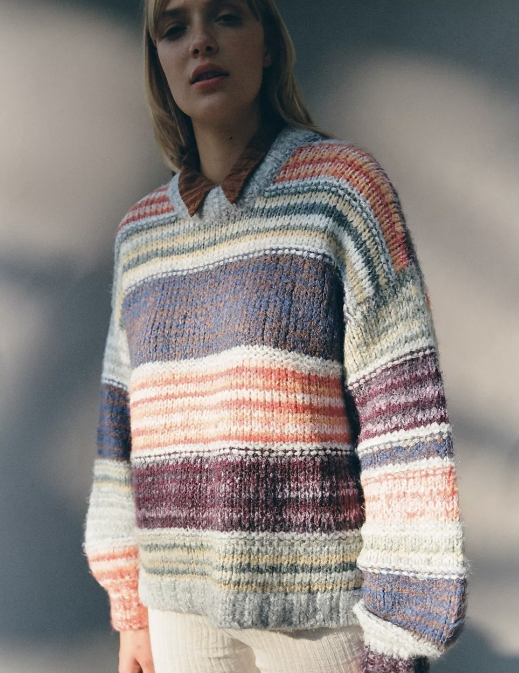 Model is wearing a knit sweat in multiple striped colors