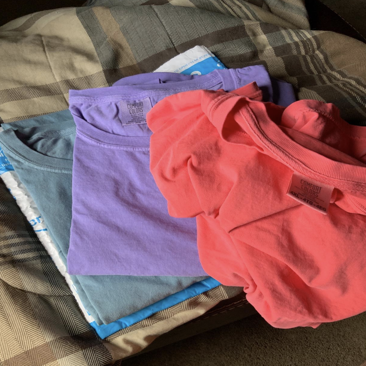 T-shirts in pink, purple, and blue