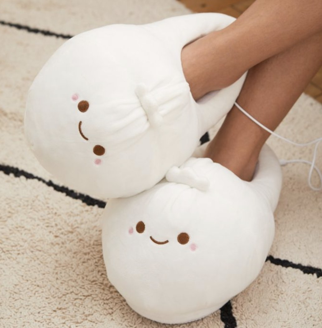 A pair of white heated slippers shaped like dumplings