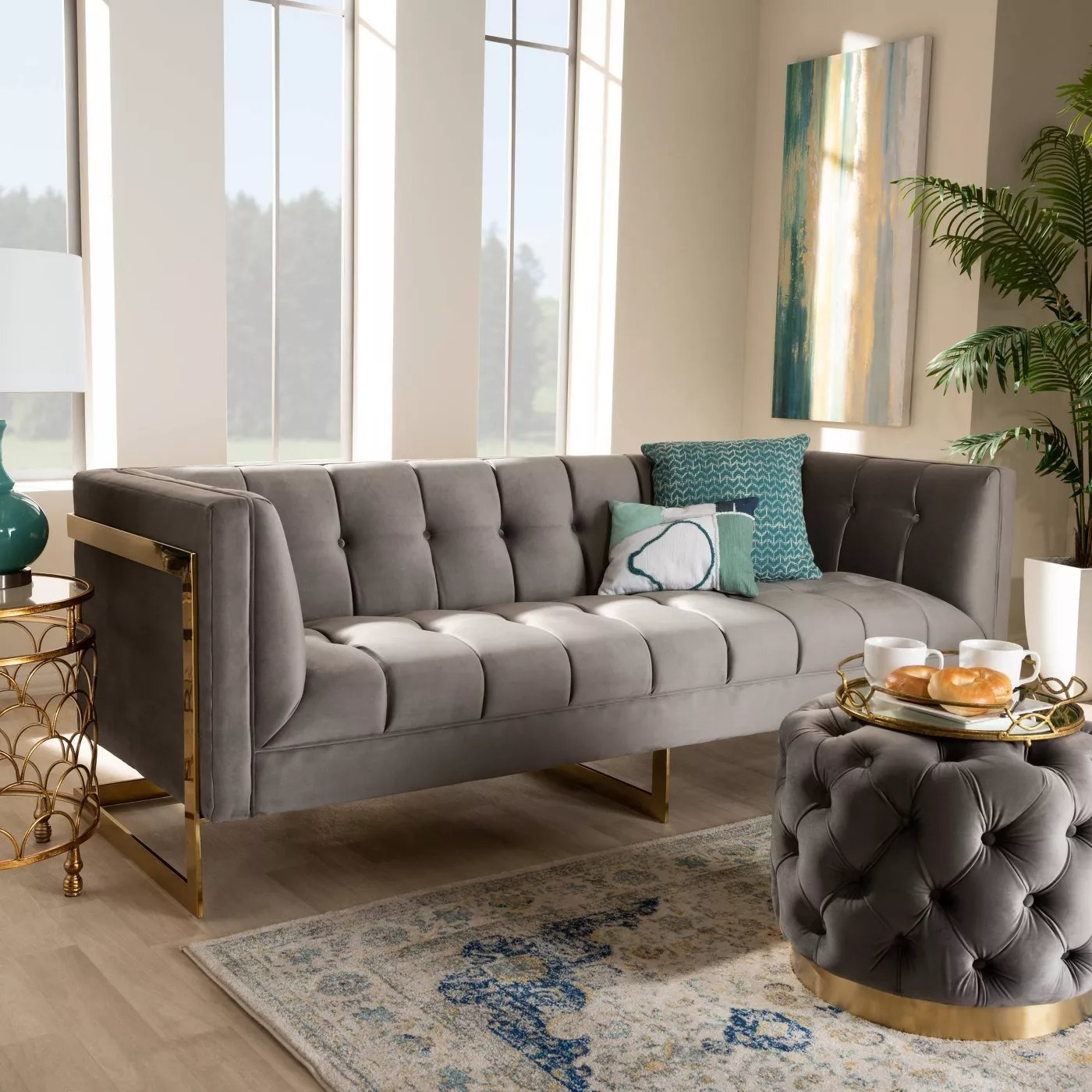 The gray couch with a gold-tone frame