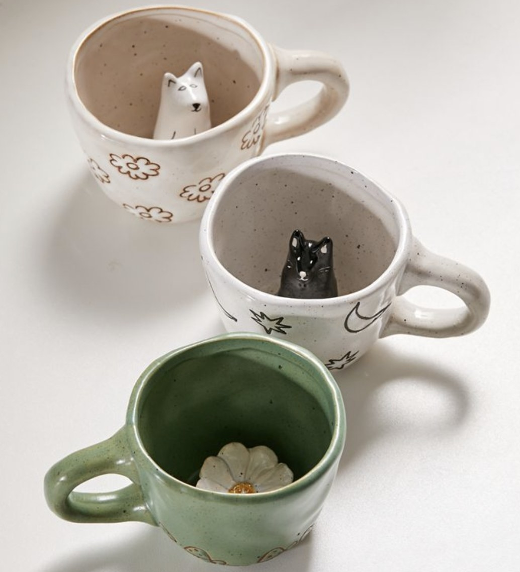 Three mugs with figurines inside