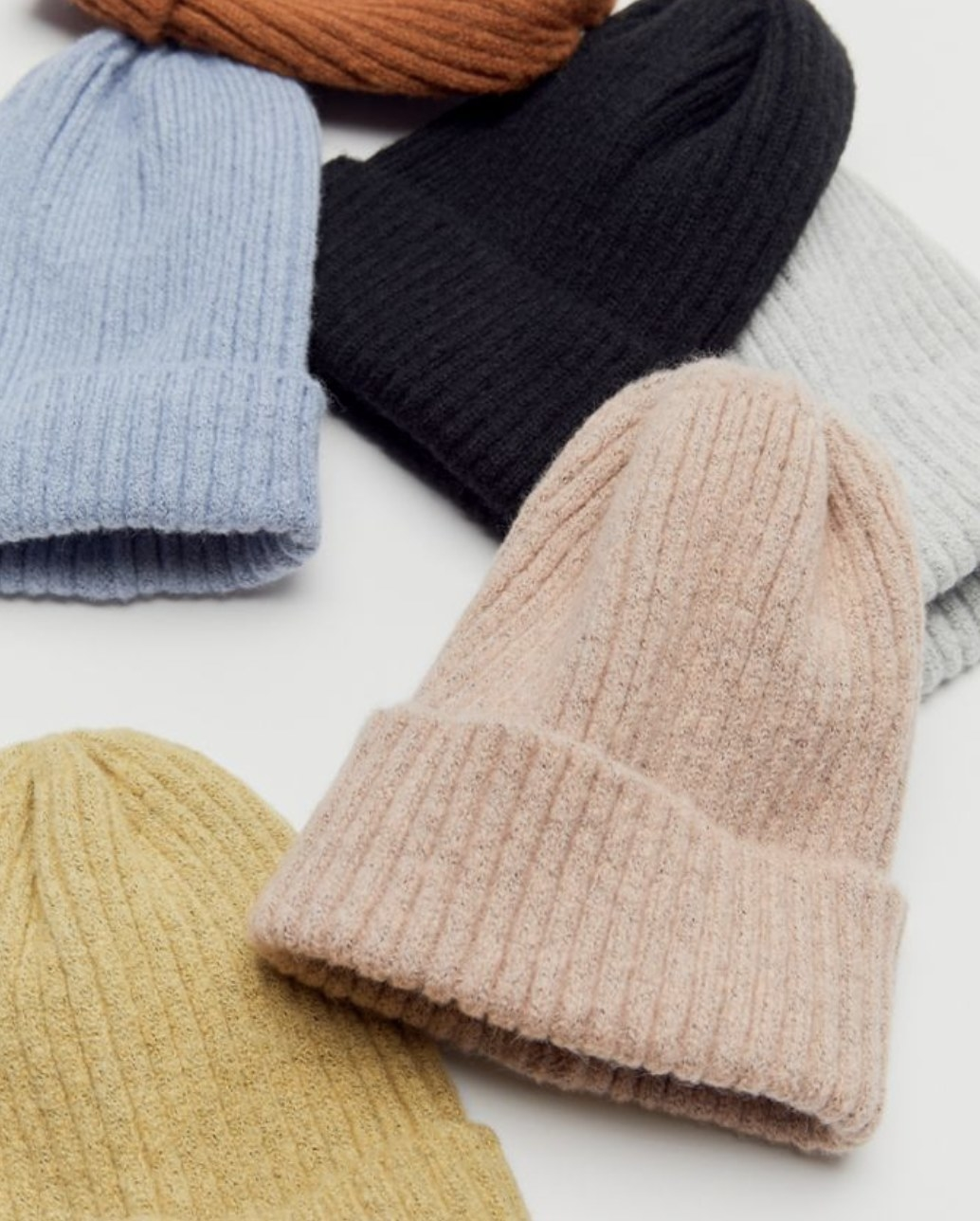 A bunch of knit beanies in various colors