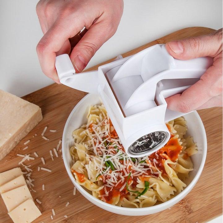 Hand turning crank on grater to churn shredded parmesan onto pasta