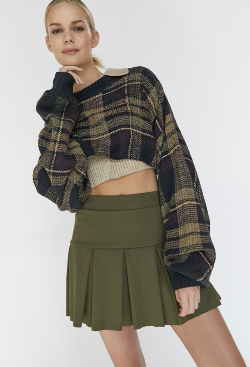 Model is wearing a forest green pleated skirt and a cropped sweater