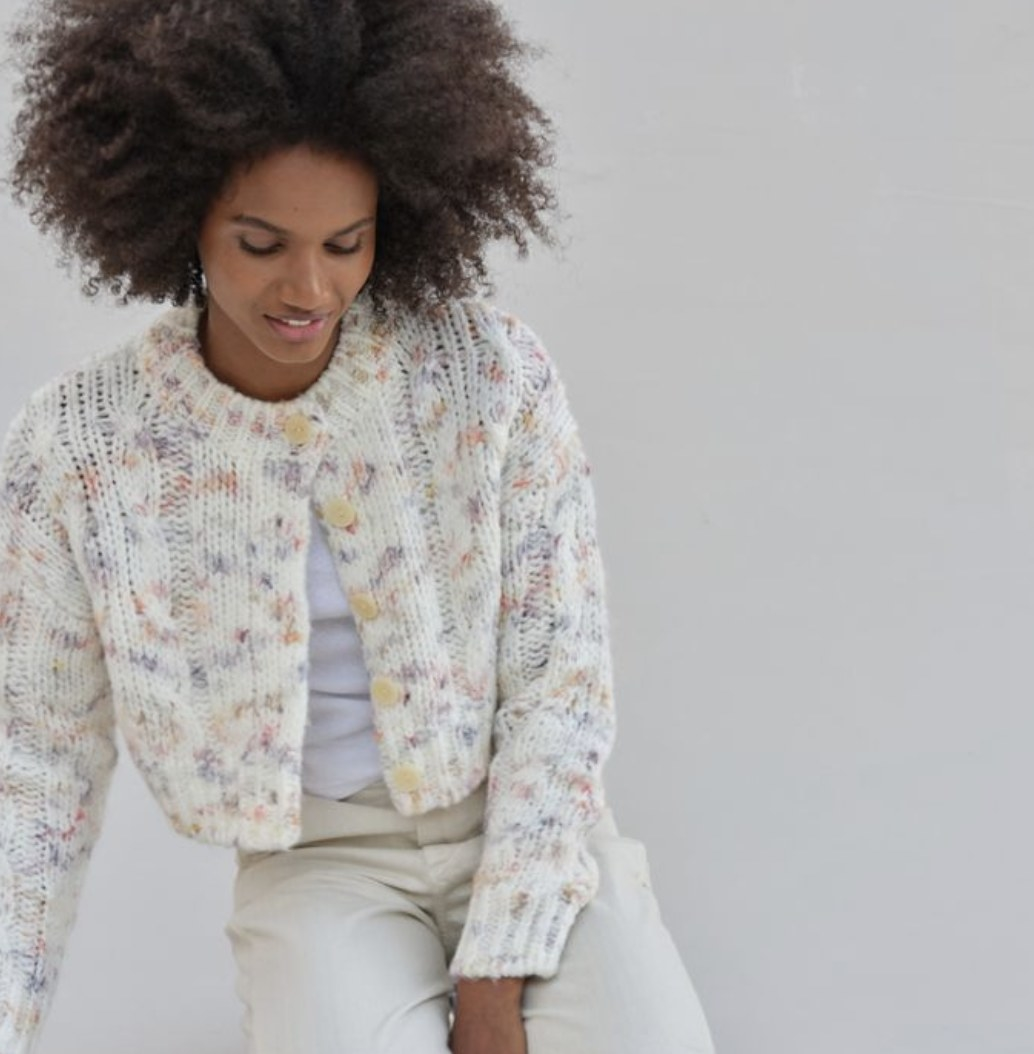 Model is wearing a white cable knit cardigan with pastel prints throughout