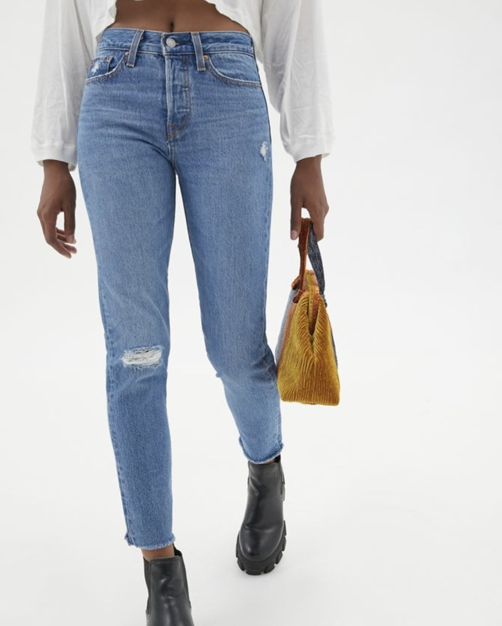 Model is wearing blue jeans, black boots, and a white top