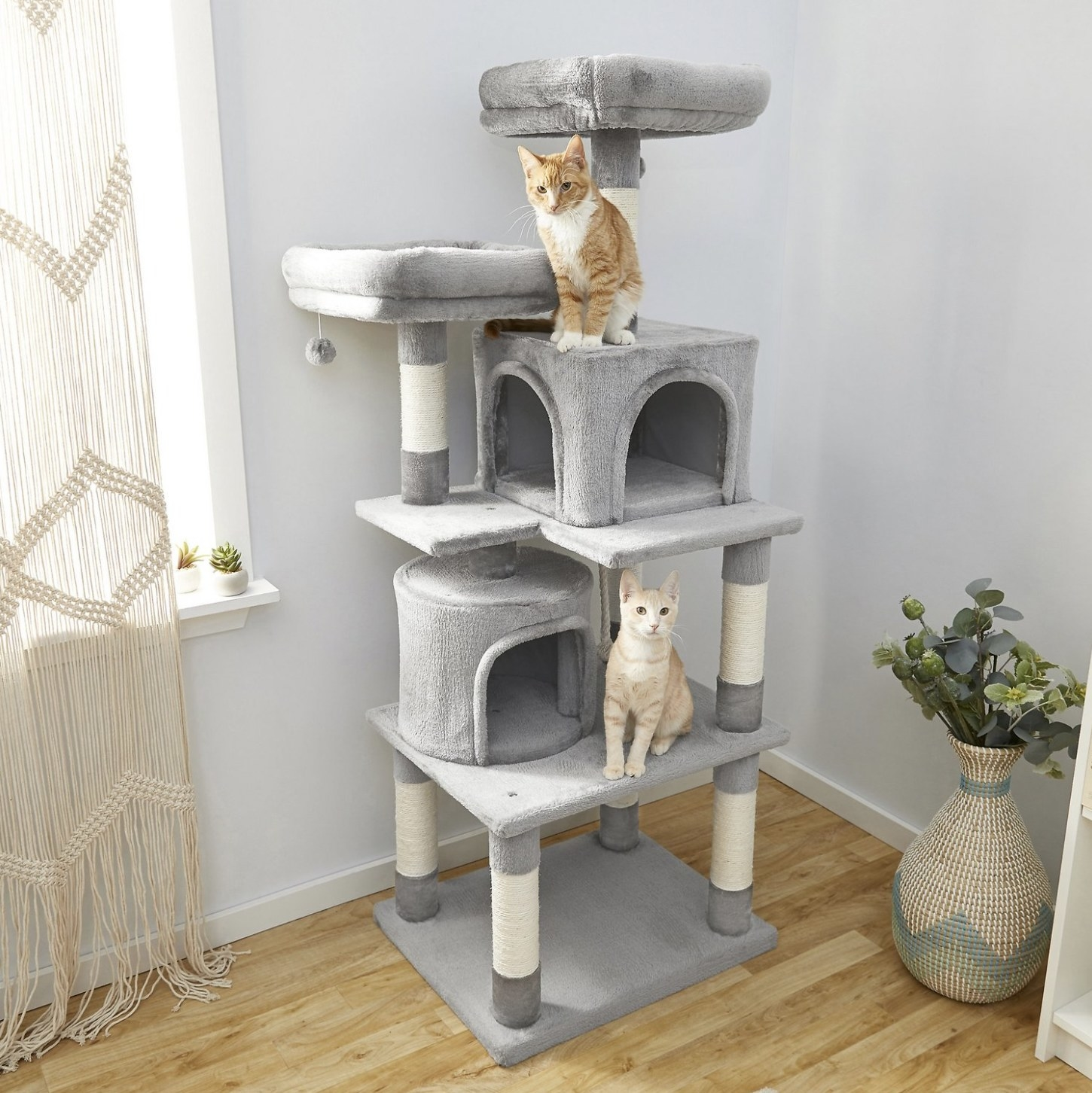 Two cats sitting on a cat tree condo