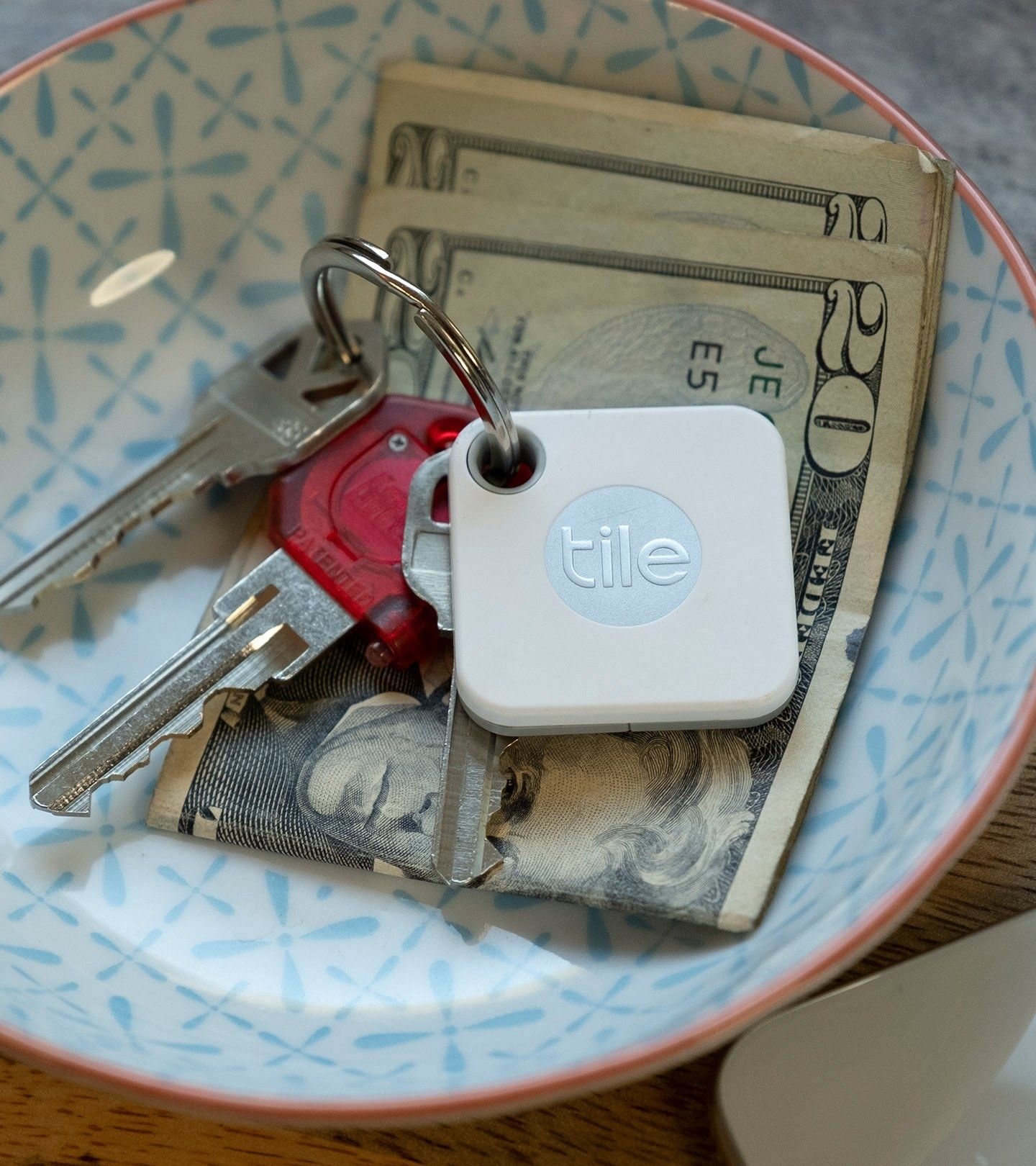 Tile tracker attached to keys in a dish with money