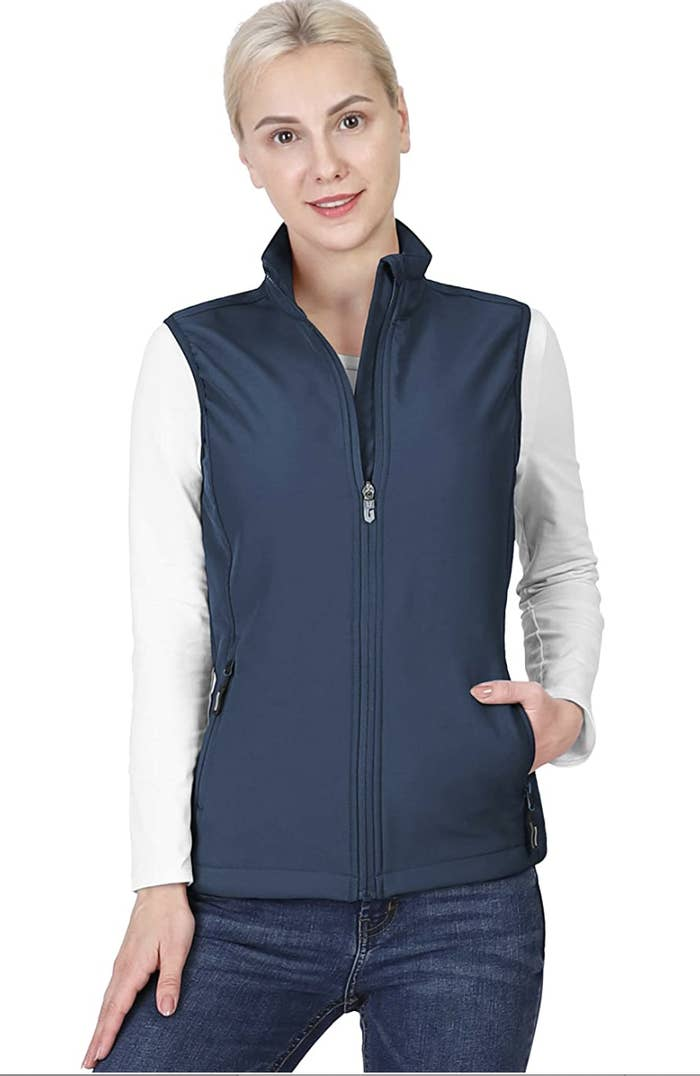 Model in a blue zip up vest with pockets and a high collar
