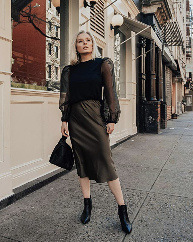a model in a black silky mid-length skirt