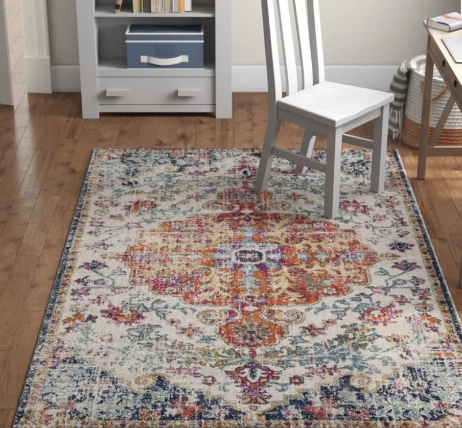 Multi colored area rug on wooden floor