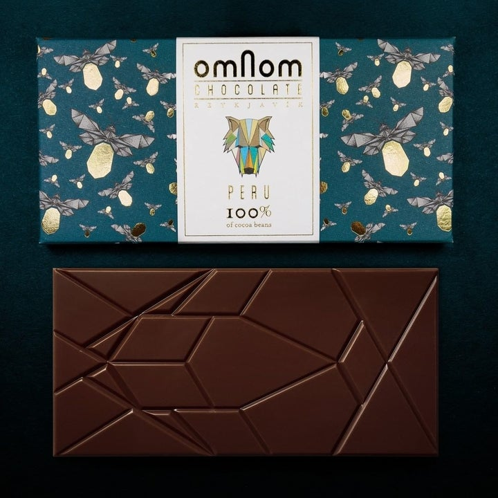 chocolate bar with geometric markings under a wrapper that has shiny gold fireflies on it