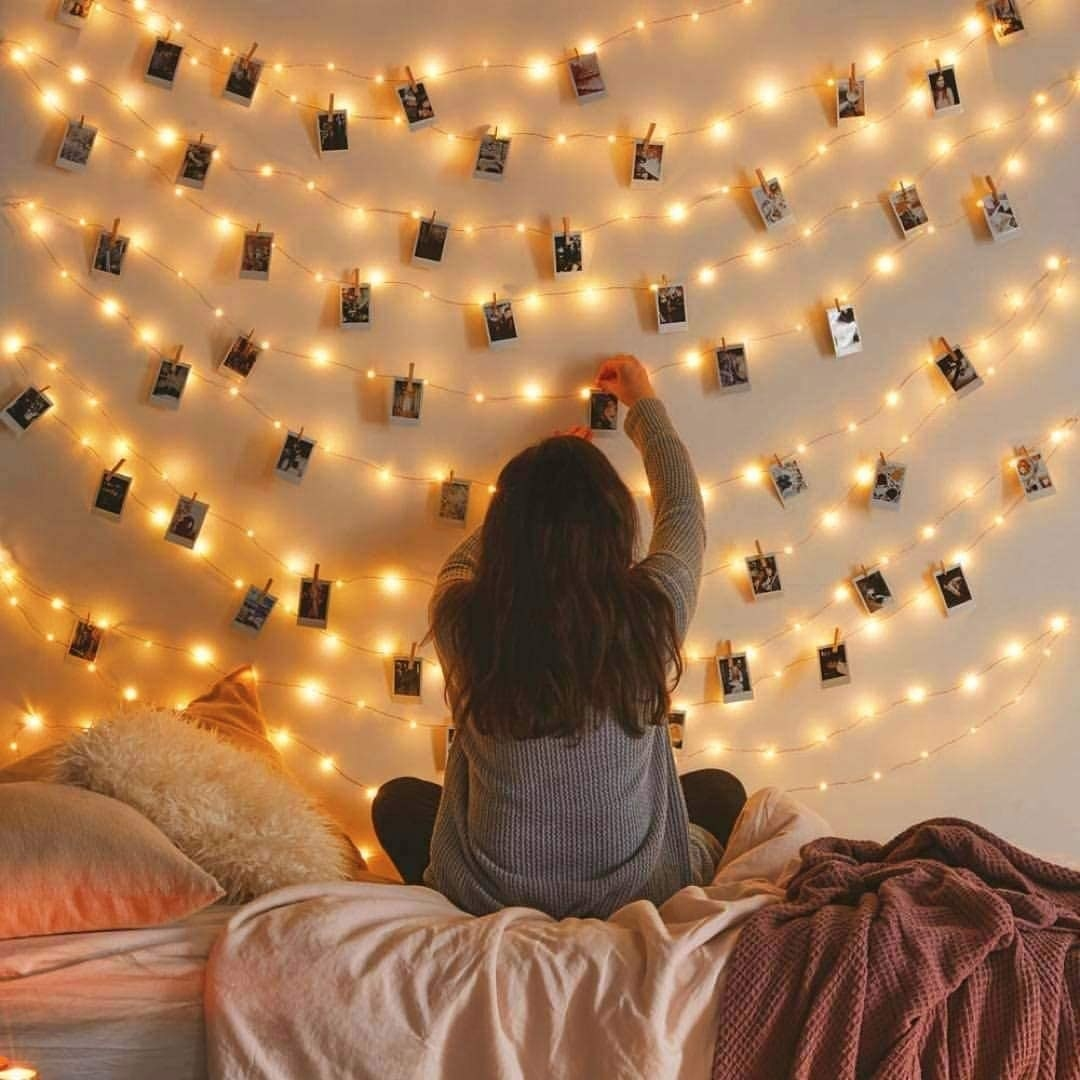 A girl pinning up pictures to her set of wall hung string lights