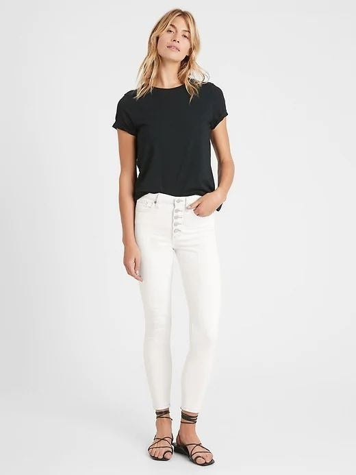 person wearing white skinny jeans and a black t-shirt