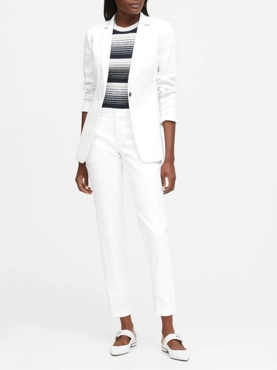 person wearing a white long blazer, white pants, striped shirt, and white shoes