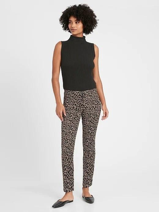 person wearing giraffe print pants and a black shirt