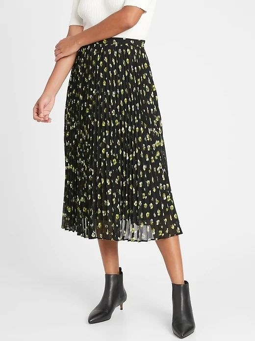 person wearing black floral midi skirt with black leather booties and a white top